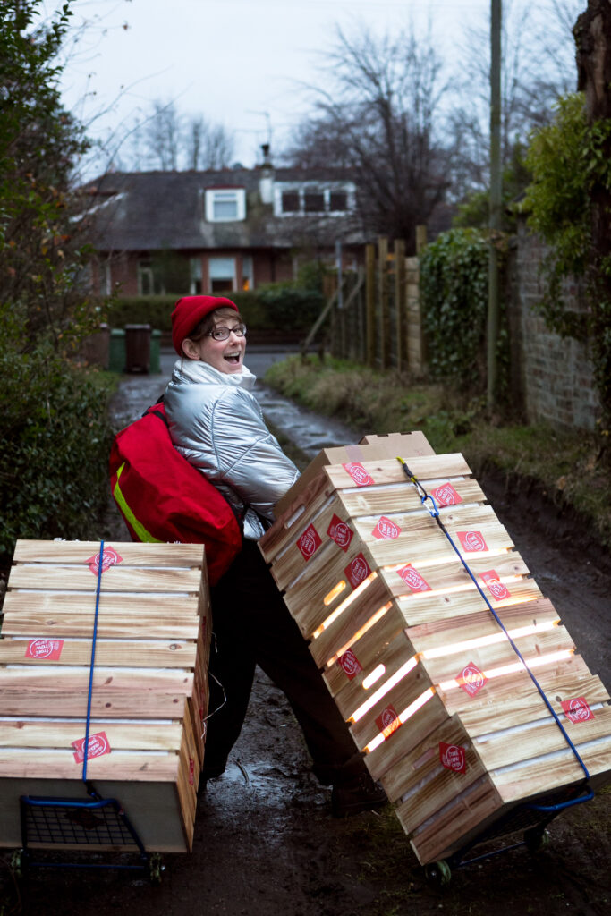 Performer Fiona Manson, wearing a silver puffer jacket and carrying a red courier delivery pack, is walking down a driveway with two stacks of crates on trolleys. She is smiling and looking backwards at the camera.