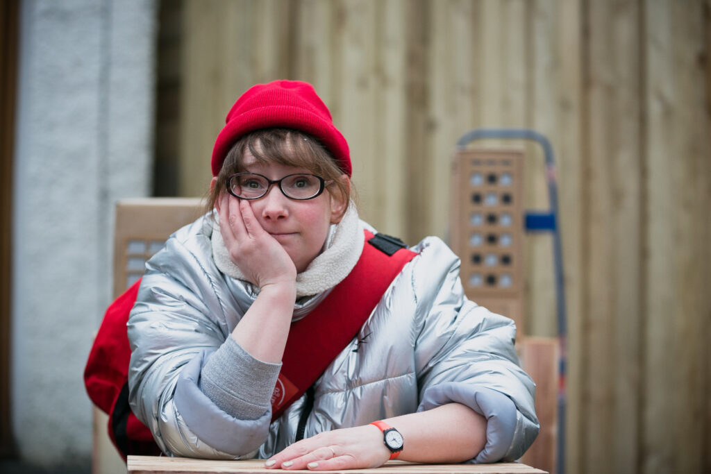 Performer Fiona Manson in a silver puffer jacket and red hat, rests her elbow on a stack of boxes she's delivering.